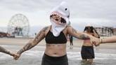 Tak hanya sekadar menceburkan diri, beberapa peserta bahkan mengenakan kostum unik seperti topi hiu dan sebagainya. (REUTERS/Caitlin Ochs)