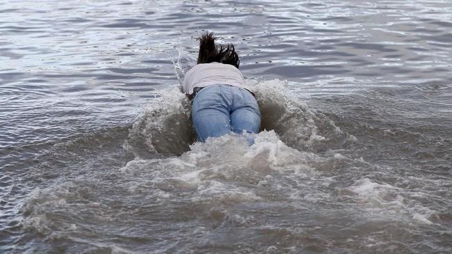 Sedangkan di Skotlandia, beberapa orang rutin mengikuti kegiatan yang dinamakan Loony Dook. (REUTERS/Russell Cheyne)