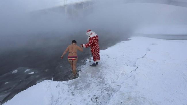 Hal yang membuat 'ritual' ini menjadi menarik adalah setiap peserta dilarang melepas pakaian. (REUTERS/Ilya Naymushin)