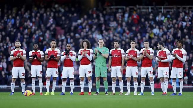 Para pemain Arsenal mengheningkan cipta jelang melawan Fulham untuk mengenang mendiang mantan presiden The Gunners Peter Hill-Wood. (REUTERS/Eddie Keogh)