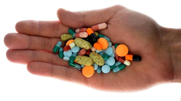 FILE PHOTO: A person holds pharmaceutical tablets and capsules in this picture illustration taken in Ljubljana September 18, 2013.  REUTERS/Srdjan Zivulovic/File Photo