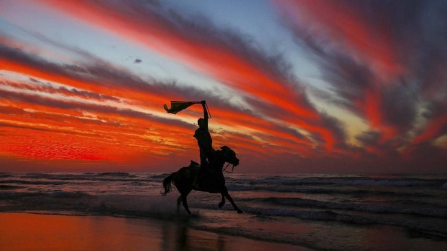 Beberapa jam sebelum perayaan tahun baru, seorang pria asal Palestina menunggangi kudanya di bagian barat kota Gaza. (Photo by MAHMUD HAMS / AFP)