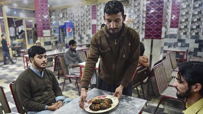 Hidangan terkenal lainnya adalah karahi. Makanan yang satu ini terbuat dari irisan daging kambing yang dimasak bersamaan dengan potongan lemak kambing. Potongan-potongan itu disajikan bersama cabai hijau dan tomat yang tak terlalu banyak.(Photo by ABDUL MAJEED / AFP)