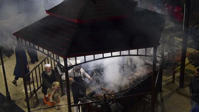 Dalam tradisi ini, potongan daging dan lemak ditusuk dengan satu batang. Tusukan itu dimasak perlahan di atas kobaran api. Minimnya rasa asin membuat sajian itu terasa lembut. (Photo by ABDUL MAJEED / AFP)
