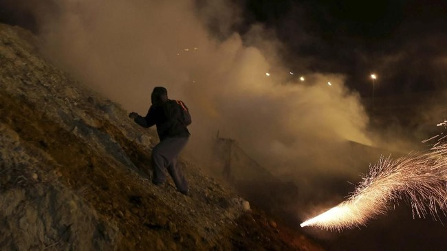 Ratusan imigran melawan lontaran gas air mata dengan melempar batu ke arah petugas Penjaga Perbatasan dan Bea Cukai (CBP) AS. (REUTERS/Mohammed Salem)
