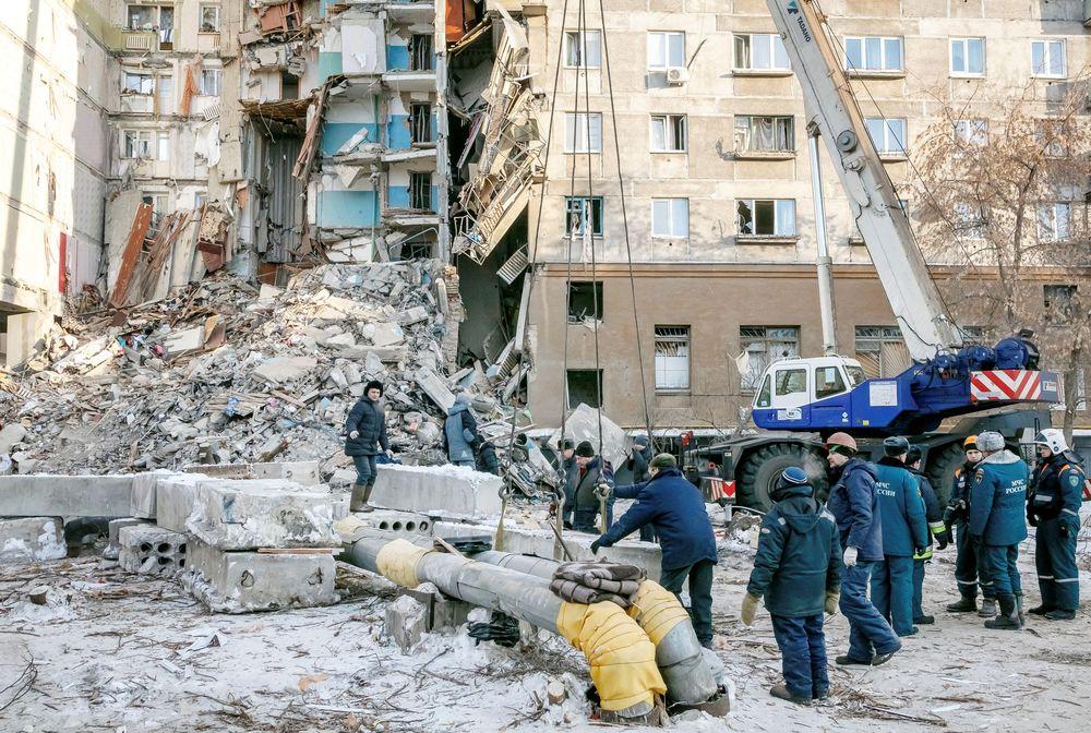 PetugasKementerian Kedaruratan Rusia mengevakuasi korban runtuhnya blok apartemen di Magnitogorsk, Rusia, Selasa (1/1/2018). Apartemen yang berjarak 1.700 kilometer dari ibu kota Moskow tersebut, runtuh akibat kebocoran gas yang dahsyat. (REUTERS/Andrey Serebryakov)