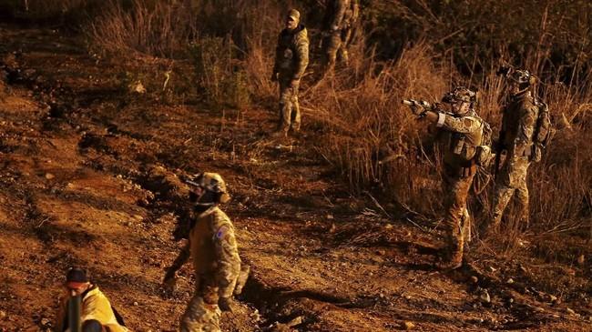 Sekelompok imigran berkeras menerobos tembok perbatasan, meski aparat AS dengan senapan serbu telah berdiri mengadang mereka. (REUTERS/Mohammed Salem)