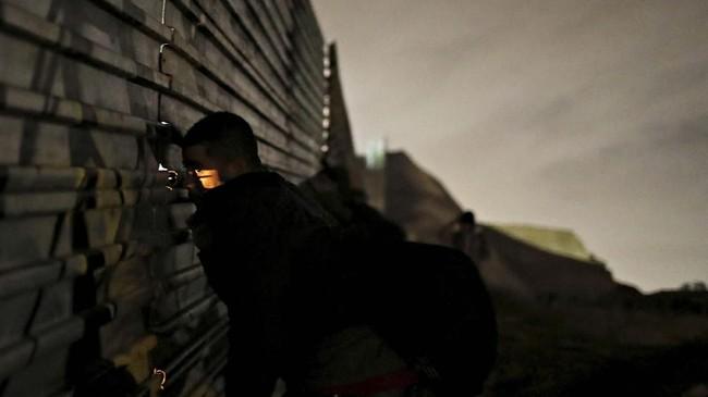 Seorang pengungsi yang menjadi bagian dari rombongan imigran yang coba menembus Amerika Serikat, melihat lewat sebuah celah di pagar di Tijuana, Meksiko. Ia dan pengungsi lainnya bersiap untuk menembus pagar itu secara ilegal. (REUTERS/Mohammed Salem)