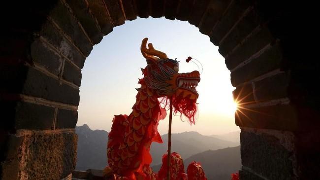 Ketika matahari terbit, para seniman mengikuti acara barongsai di Tembok Besar China bagian Mutianyu di distrik Huairou, Beijing, China. (Xiangdong/Qianlong.com via REUTERS)