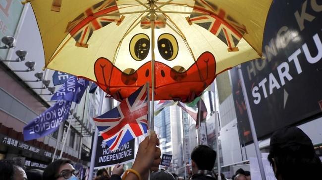 Seorang pendukung gerakan kemerdekaan membentangkan payung berhiaskan bendera Inggris ketika mengikuti acara protes di Tahun Baru di Hong Kong, China.(REUTERS/Tyrone Siu)