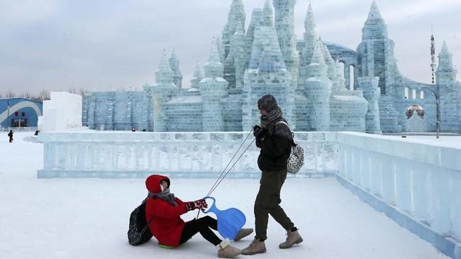 Turis berfoto di depan bangunan yang berasal dari pahatan es di festival musim dingin di Harbin, China.