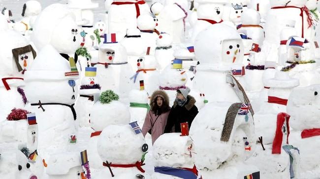 Pahatan es manusia salju yang menjadi salah satu sudut favorit berfoto di festival musim dingin di Harbin, China.