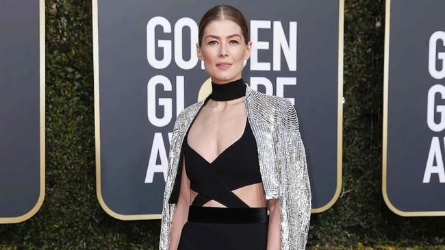 Rosamund Pike menghadiri Golden Globes 2019 berbalut gaun hitam seksi dari Givenchy Haute Couture. Nominasi Best Actress in a Motion Picture - Drama ini memadukan gaun itu dengan jaket payet yang berkilauan. (REUTERS/Mike Blake)