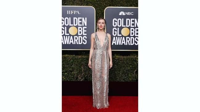 Saoirse Ronan mengenakan gaun perak dengan garis leher berpotongan rendah dari Gucci dipadukan riasan minimalis. Gaun transparan ini membuat kulitnya tampak samar-samar di balik busana. (REUTERS/Mike Blake)