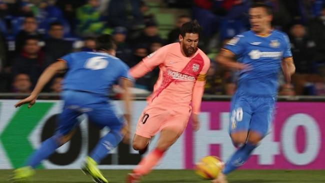 Lionel Messi berusaha melewati dua pemain Getafe Nemanja Maksimovic dan Leandro Cabrera. Messi kini memuncaki top skor Liga Spanyol dengan torehan 16 gol. (REUTERS/Sergio Perez)
