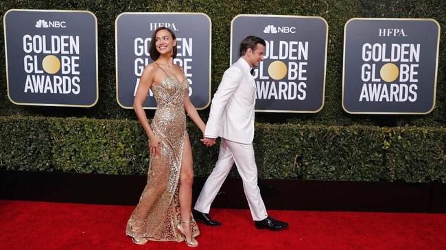 Irina Shayk berjalan dengan mesra bersama Bradley Cooper di karpet merah Golden Globes 2019. Model Rusia ini memakai gaun emas transparan denganslittinggi. (REUTERS/Mike Blake)