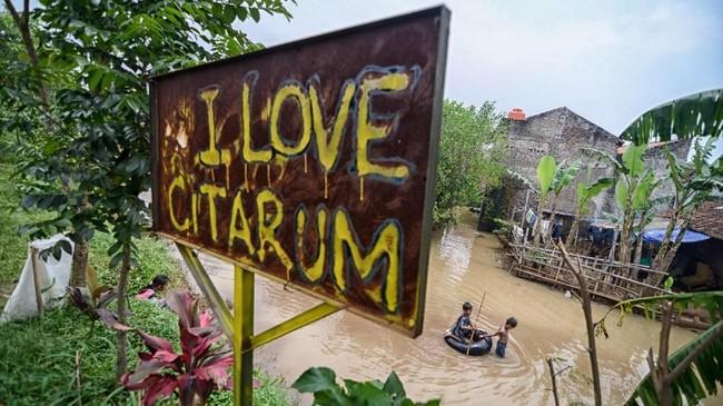 Dua orang anak bermain saat banjir di Kampung Bojong Asih, Desa Dayeuhkolot, Kabupaten Bandung,6 Maret 2018. Untuk menanggulangi banjir, Pemprov Jabar menggunakan segala cara termasuk lewat pembangunan kolam retensi Cieunteung.(ANTARA FOTO/Raisan Al Faris)