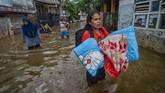 Seorang warga membawa perlengkapan tidur untuk mengungsi dari rumahnya yang terendam banjir di Kampung Bojong Asih, Dayeuhkolot, Kabupaten Bandung, 12November 2018. (ANTARA FOTO/Raisan Al Farisi)