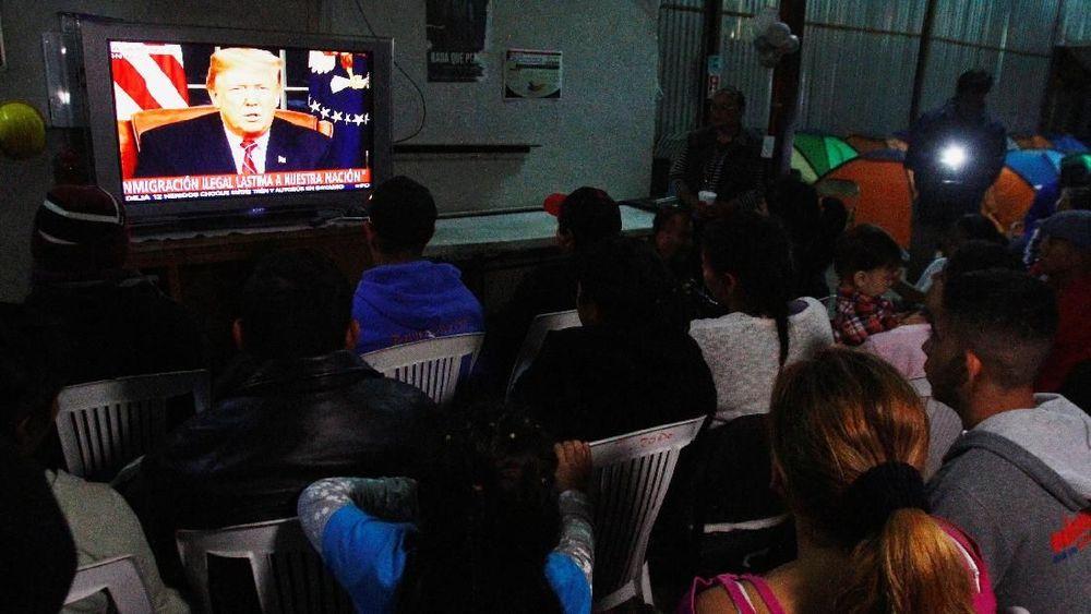 Kelompok karavan migranAmerika Tengah dalam perjalanan ke AS menonton pidato televisi Presiden AS Donald trump di tempat penampungan 'Juventud 2000' di Tijuana, Meksiko, 8 Januari 2019. Reuters/Jorge Duenes