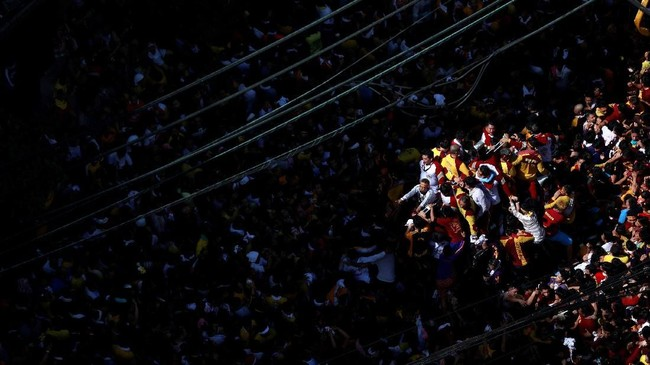 Jutaan umat Katolik ini bukan hanya datang dari Manila, namun juga seluruh penjuru Filipina. Patung Black Nazarene yang menggambarkan Yesus tengah memapah salib hitam diyakini banyak mendatangkan keajaiban dan keberkahan. (REUTERS/Soe Zeya Tun)