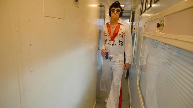 Di acara, para Elvis dan Priscilla Presley menari-nari diiringi musik, sembari mengobrol dan menikmati santapan. Wali kota Parkes berbicara di panggung untuk menyampaikan terima kasih dan penghargaan atas kehadiran para peserta. (Photo by SAEED KHAN / AFP)