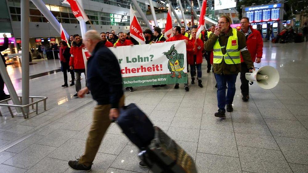 Seorang penumpang melintas di depan keramaian serikat buruh yang berdemo di Bandara Duesseldorf, Jerman, Kamis (10/1/2019). (Reuters/Wolfgang Rattay)