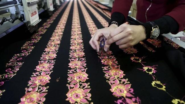 Warga Palestina bekerja pada selembar kain panjang yang digunakan untuk membuat gaun tradisional di sebuah pabrik di Ramallah.(REUTERS/Raneen Sawafta)