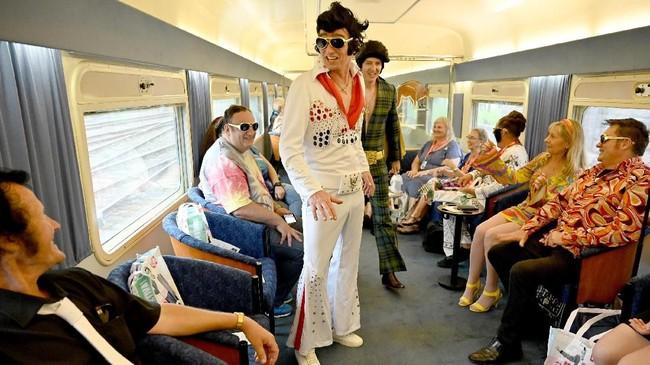 Para Elvis Presley menjadi atraksi tersendiri bagi para pengguna kereta lainnya. (Photo by PETER PARKS / AFP)