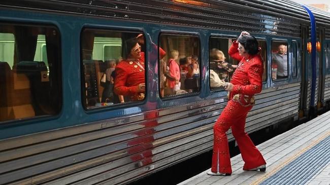 Seorang peniru Elvis Presley yang mengenakan kostum berwarna merah manyala sedang berkaca di salah satu jendela kereta dan merapikan rambut. (Photo by PETER PARKS / AFP)