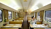 Seorang penggemar Elvis Presley duduk di dalam kereta sambil menelepon. Ia sedang dalam perjalanan menuju festival untuk berjumpa dengan Elvis-Elvis lain. (Photo by PETER PARKS / AFP)