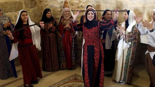 Wanita Palestina beramai-ramai merayakan dan menghormati Rashida Tlaib atas aksinya mengenakan thobe--pakaian tradisional Palestina--saat pengambilan sumpah jabatan Kongres Amerika Serikat. (REUTERS/Mohamad Torokman)