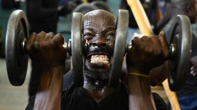 Seorang pria mengangkat beban saat berolahraga di sebuah pusat kebugaran di Nairobi, Kenya. (AFP/Simon Maina)