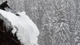 Salju tebal yang berada di bangunan membahayakan karena bisa membuat atap bangunan runtuh karena tidak sanggup menahan bobotnya. (REUTERS/Leonhard Foeger)