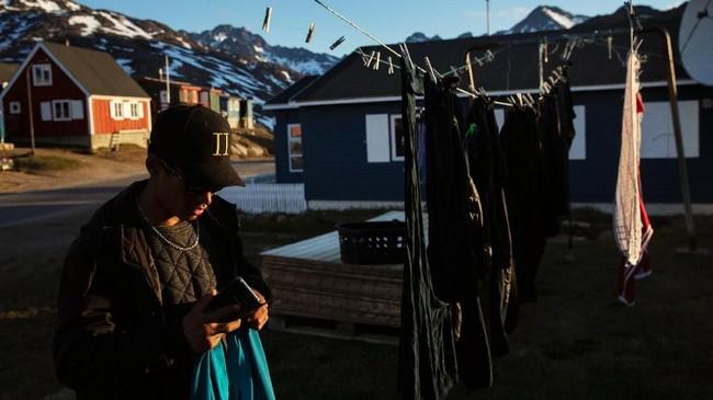 Seorang warga mencuci baju saat matahari bersinar hangat di kota Tasiilaq, Greenland.