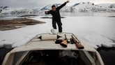Salah seorang warga di kotaTasiilaq, naik kapal untukmencari telur burung puffin, salah satu dari sekian banyak mata pencarian penduduk di Greenland.