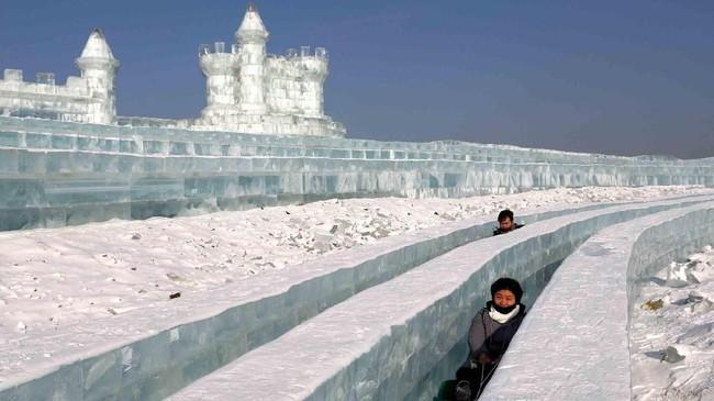 Para pengunjung berada di antara patung-patung es di festival es di Harbin, Provinsi Heilongjiang, China. (Reuters/Tyrone Siu)