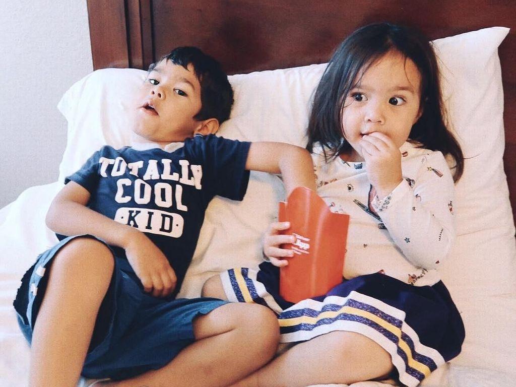 Dua bersaudara ini kompak makan kentang goreng di tempat tidur. Duh, nikmatnya! Foto: Instagram zrofficial
