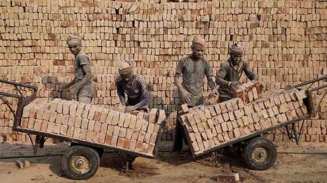 Seorang pekerja pabrik batu bata menyusun batu bata ke dalam gerobak di Dhaka, Bangladesh. (Reuters/Mohammad Ponir Hossain)