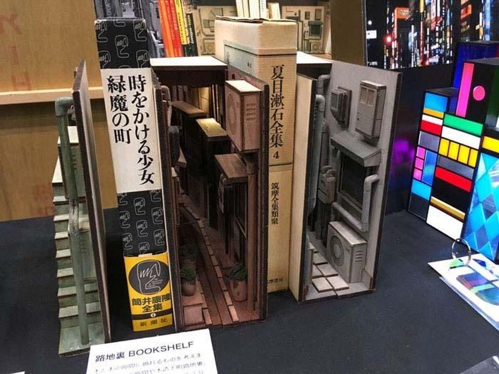 Seorang seniman asal Jepang membuat mini diorama untuk pameran internasional. Ia membuat pembatas rak buku yang unik. Istimewa/Boredpanda.