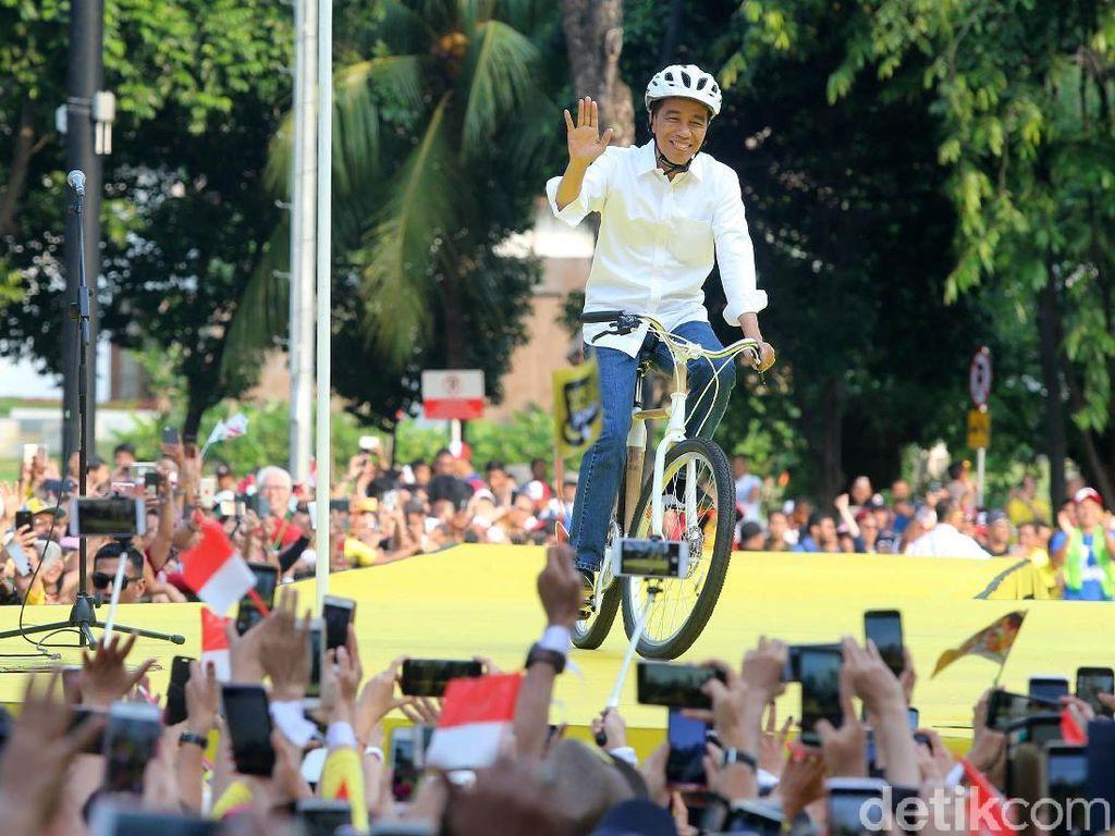 Jokowi melambaikan tangan kepada pendukungnya.