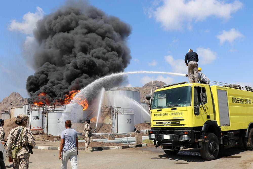 Petugas pemadam kebakaran berusaha mendinginkan tangki penyimpanan minyak yang berdekatan dengan tangki yangterbakar kemarin di kilang minyak Aden Yaman (12/1/2018). Sebuah ledakan menyebabkan kebakaran terjadi di kilang minyak utama milik Yaman di Kota Aden. (REUTERS / Fawaz Salman)