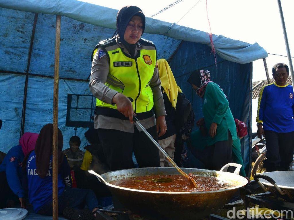 Polisi ikut membantu menyiapkan makanan untuk pengungsi.