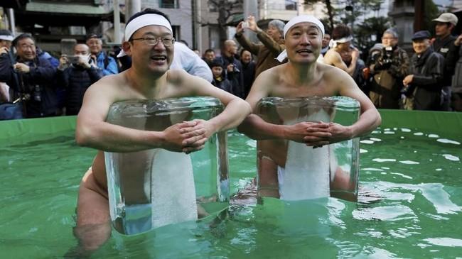 Dua orang pria memeluk sebuah balok es demi kesehatan dan keberuntungan di tahun baru.