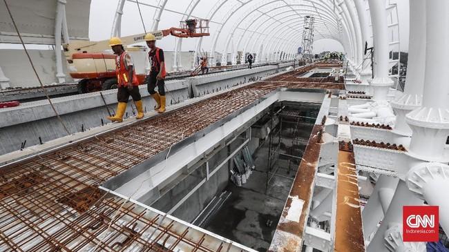 Pekerja menyelesaikan proyek stasiun kereta api ringan (Light Rail Transit/LRT) di Stasiun LRT Taman Mini, Jakarta, Senin (14/1). (CNNIndonesia/Safir Makki).