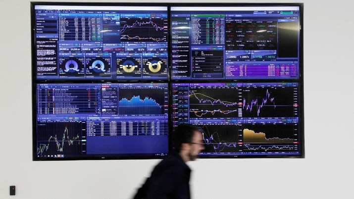 Traders work at their desks whilst screens show market data at CMC Markets in London, Britain, January 16, 2019. REUTERS/John Sibley