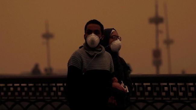 Cuaca di Kota Kairo mendadak menjadi kemerahan karena cahaya matahari terhalang badai pasir. (REUTERS/Amr Abdallah Dalsh)