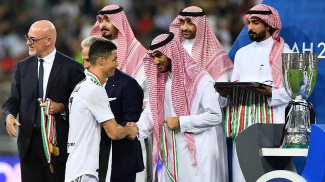 Cristiano Ronaldo menerima medali usai membawa Juventus menang atas AC Milan di Piala Super Italia 2018. Ini adalah trofi pertama Ronaldo bersama Juventus sejak dibeli dari Real Madrid awal musim ini. (REUTERS/Waleed Ali)