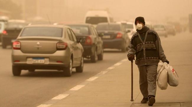 Penduduk Kairo yang terpaksa harus beraktivitas di luar ruangan di tengah badai pasir harus mengenakan masker dan jaket. (REUTERS/Mohamed Abd El Ghany)