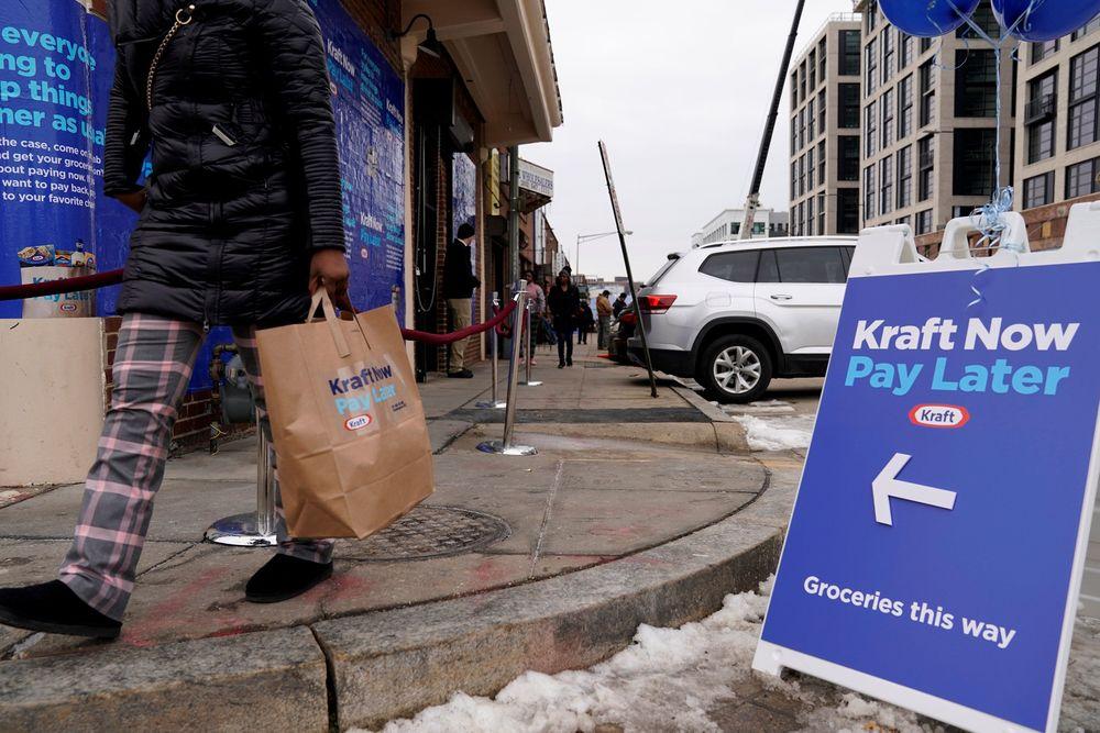 Seorang pekerja federalmembawa tas belanjaan gratis dari Kraft Foods di Washington, AS, Kamis (17/1/2019).Kraft membuka toko bahan makanan gratis