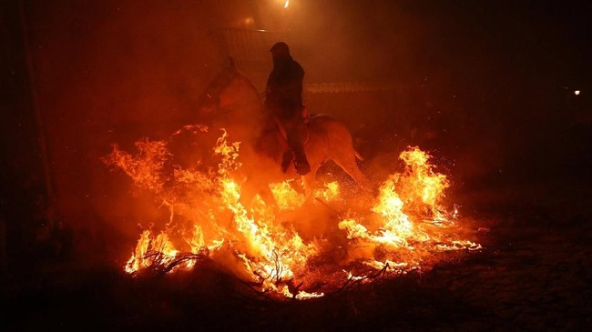 Satu per satu, para penunggang kuda memimpin hewan mereka menembus kobaran api. Festival ini diyakini telah dilakukan selama ratusan tahun.(REUTERS/Susana Vera)